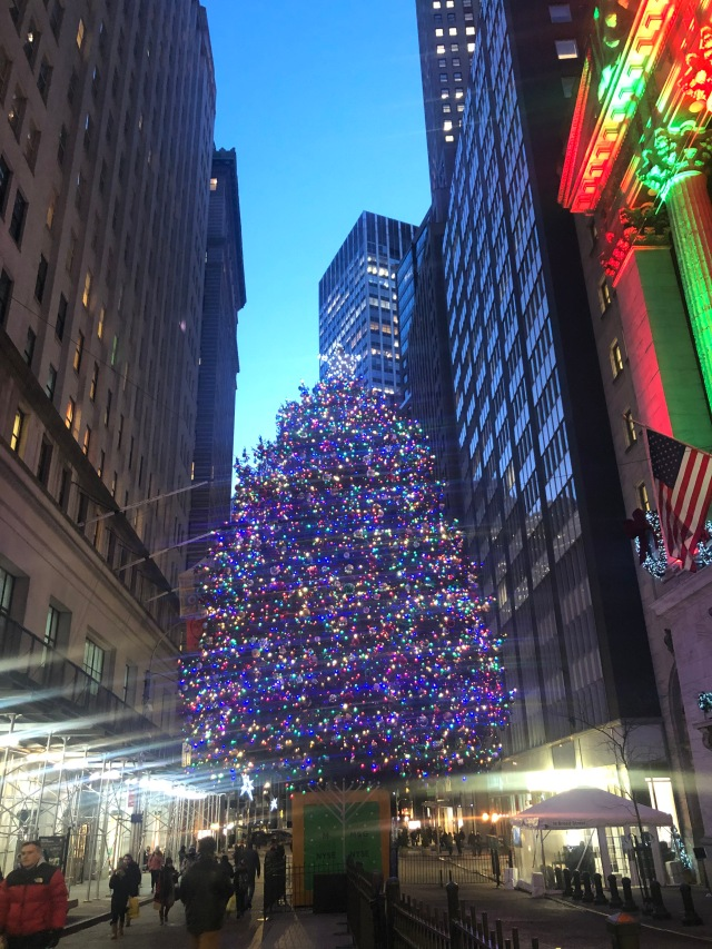 A large decorated Christmas tree with a menorah in front of it in early evening outside the New York Stock Exchange.